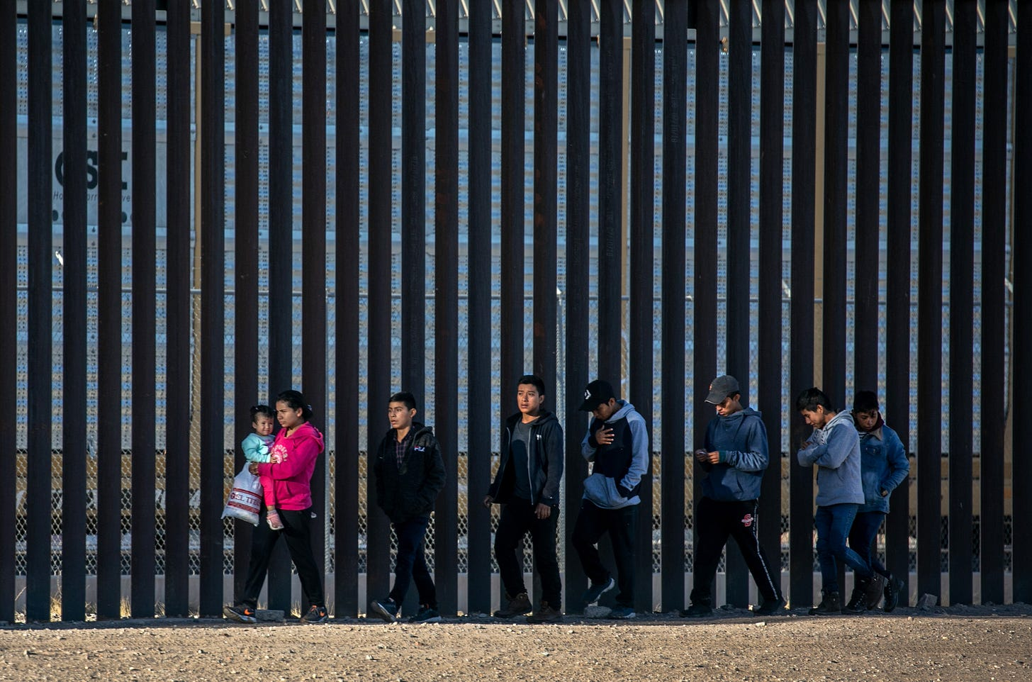 Undocumented immigrants walk along the U.S.-Mexico border wall after they ran across the shallow Rio Grande into El Paso on March 17, 2021 in Ciudad Juarez, Mexico. U.S. immigration officials are dealing with an immigrant surge along the southwest border with Mexico. (Photo by John Moore/Getty Images)