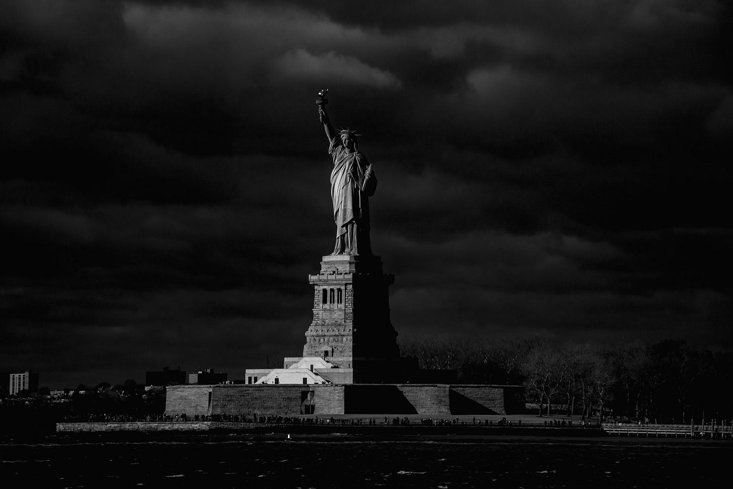 A black and white photo of the Statue of Liberty against a dark sky.