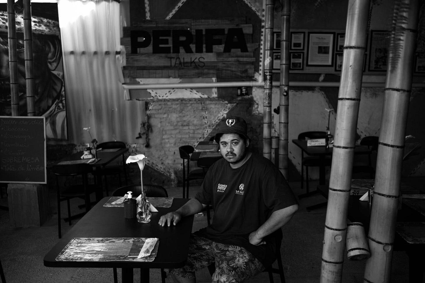 Imagem em preto e branco mostra Thiago Vinicius sentado em mesa de restaurante, ao fundo se lê um letreiro escrito Perifa Talks