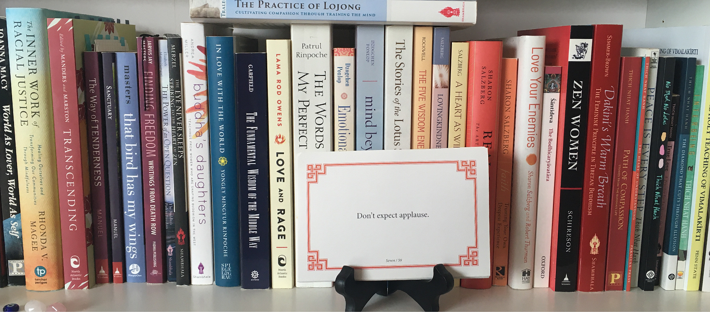 """Photo of the lojong slogan card """"Don't expect applause"""" sitting on a white bookcase surrounded by Buddhist books."""