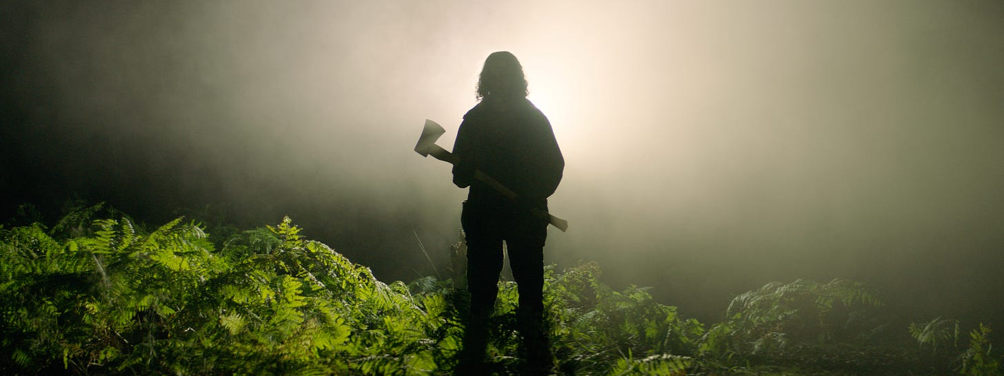 """From the film """"In the Earth"""": The silhouette of a man carrying an axe appears through light and fog in the middle of deep forest shrubbery."""