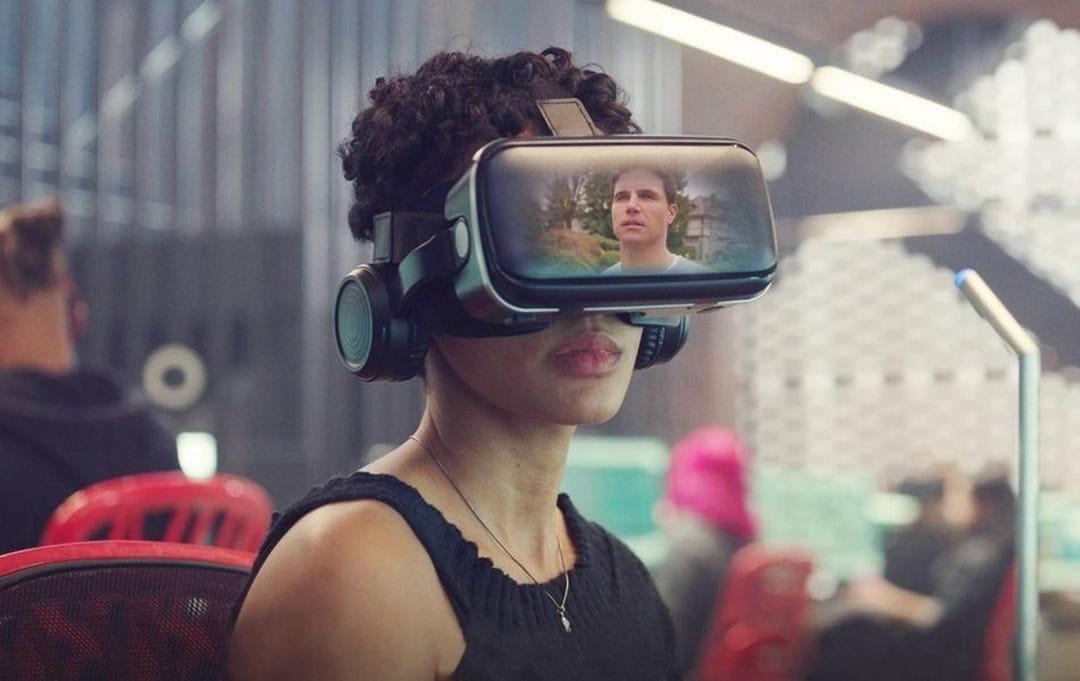 Imagem de uma mulher num escritório usando um dispositivo VR para observar a imagem de um homem, mostrado na tela dos óculos