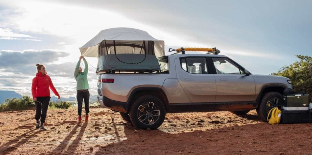 women setting up rooftop tent on rivian truck
