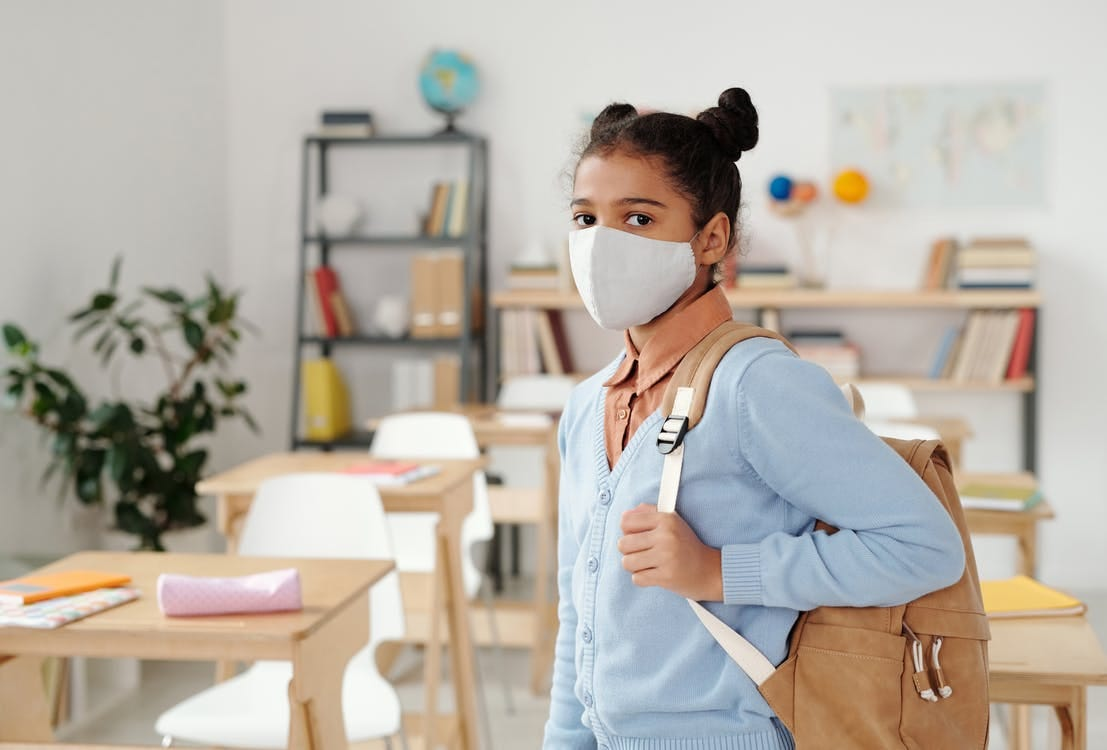 Woman in Blue Long Sleeve Shirt Wearing White Mask