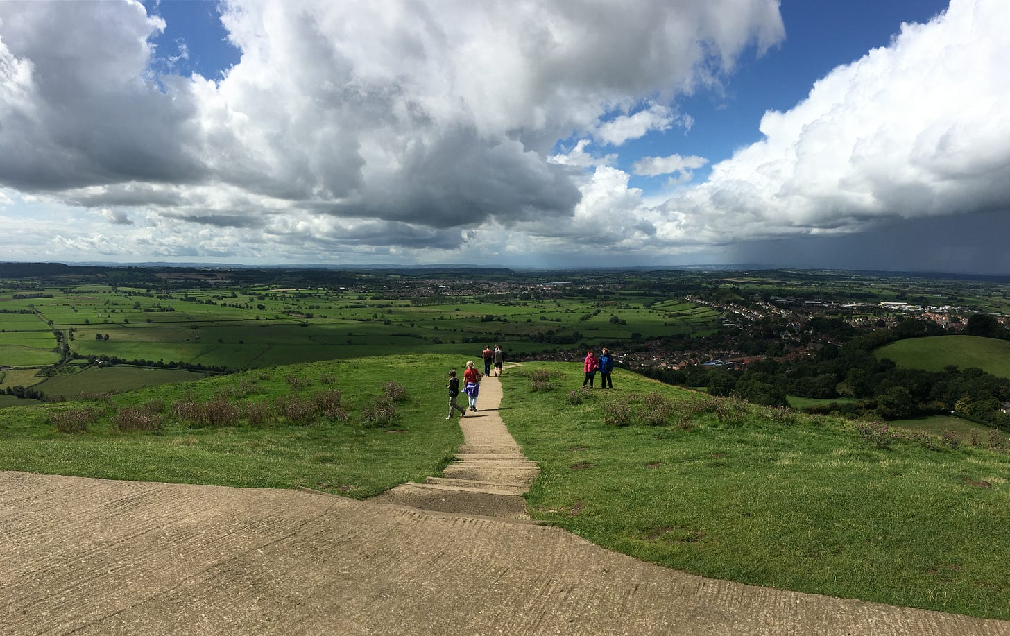 Partly cloudy sky over a vast expanse of green. A dirt path cuts down a hill in the center of the image, toward towns and houses below. A few people are ahead on the path.