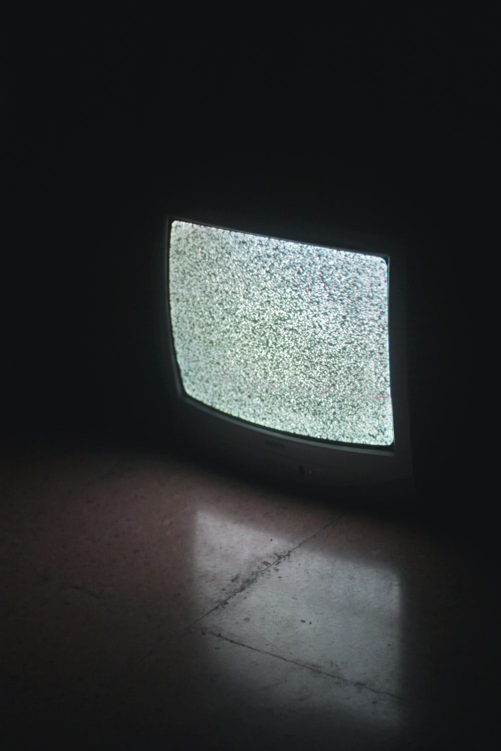 gray crt tv turned on in a dark room