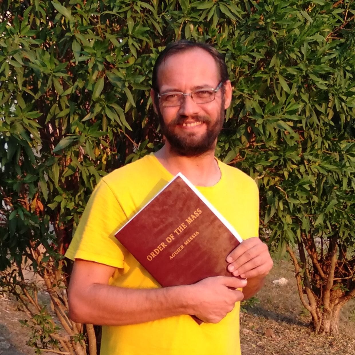 May be an image of 1 person, standing, outerwear, book and text that says 'MASS THE MESSIA OF ORDER AGUIER'