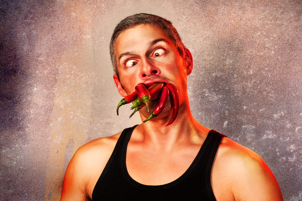 ridiculous expression of a man with lots of hot chillies in his mouth
