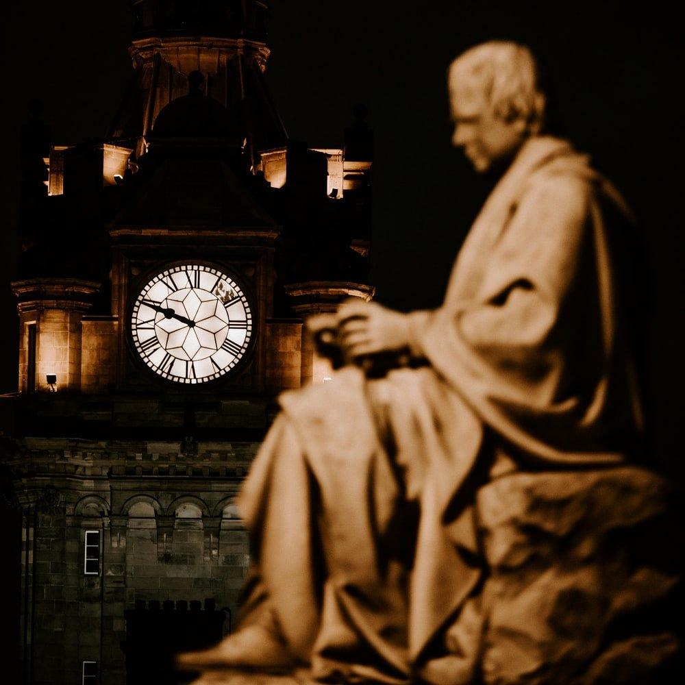grey analog clock near statue