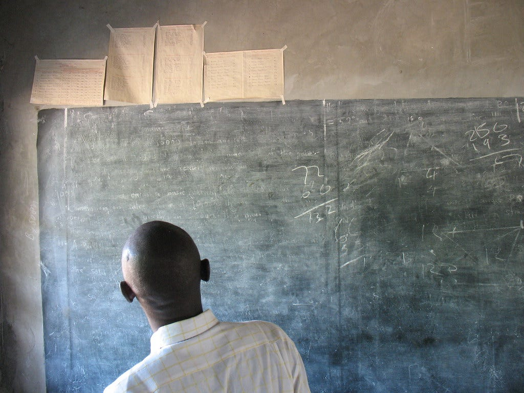 """Back of someone's head as they read a dusty chalkboard. """"Chalkboard"""" by aaron.knox is licensed under CC BY-NC-SA 2.0"""