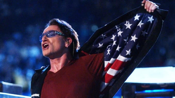 """Bono, lead singer of U2, displays American flag lining in his jacket after singing """"Where The Streets Have No Name,"""" during the halftime show of Super Bowl XXXVI in the Superdome, New Orleans, Louisiana, February 3, 2002."""