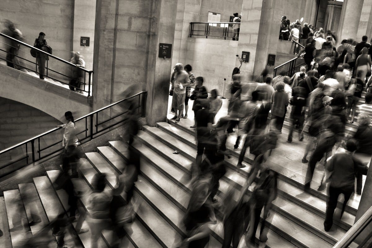 black and white image of a crowd climbing stairs on article by Larry G. Maguire