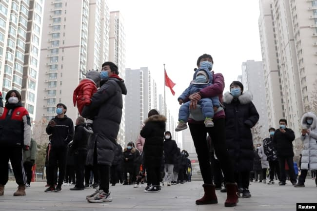 People practice social distancing as they line up for a second round of citywide nucleic acid testing at a residential compound, following new COVID-19 cases in Shijiazhuang, Hebei province, China on Jan. 12, 2021.