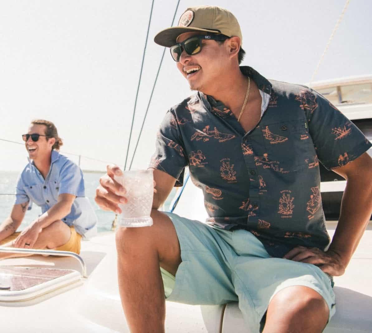 man sitting on boat wearing howler bros horizon hybrid shorts