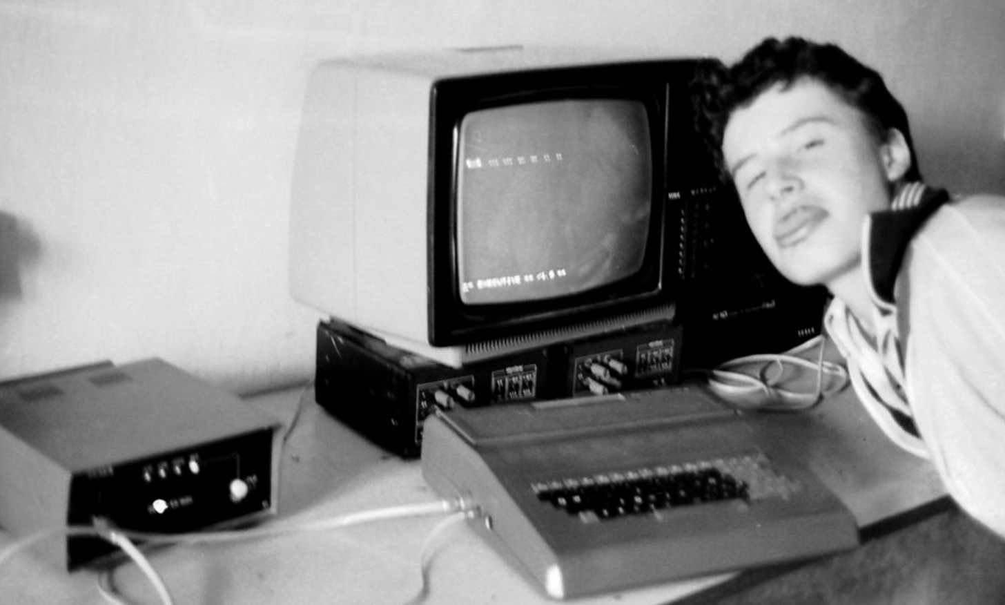 A teenager sticks his tongue out at the camera, sitting in front of a clunky 1980s computer with CRT screen.