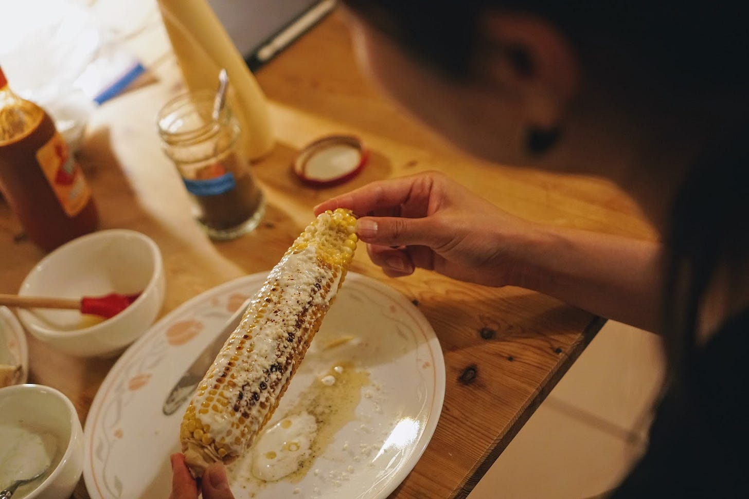 Grilled corn topped with butter and cheese in Yoko's hands