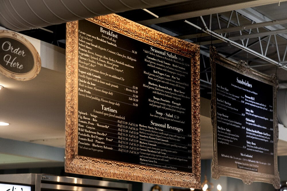 Two large frames showcase the menu at Amélie's Bakery in Atlanta.