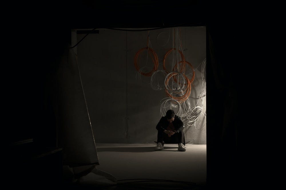 man sitting on his skateboard in a dark room