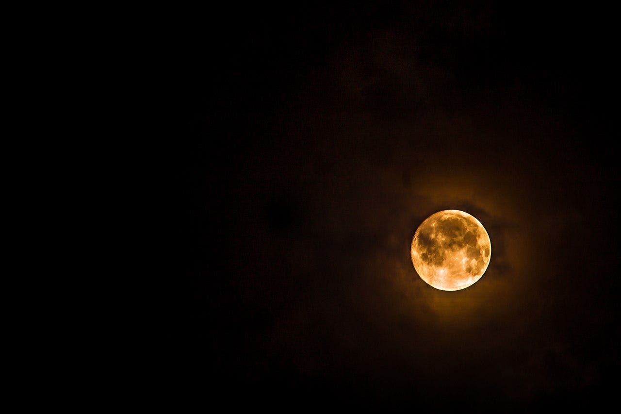 A yellow moon against a dark night sky