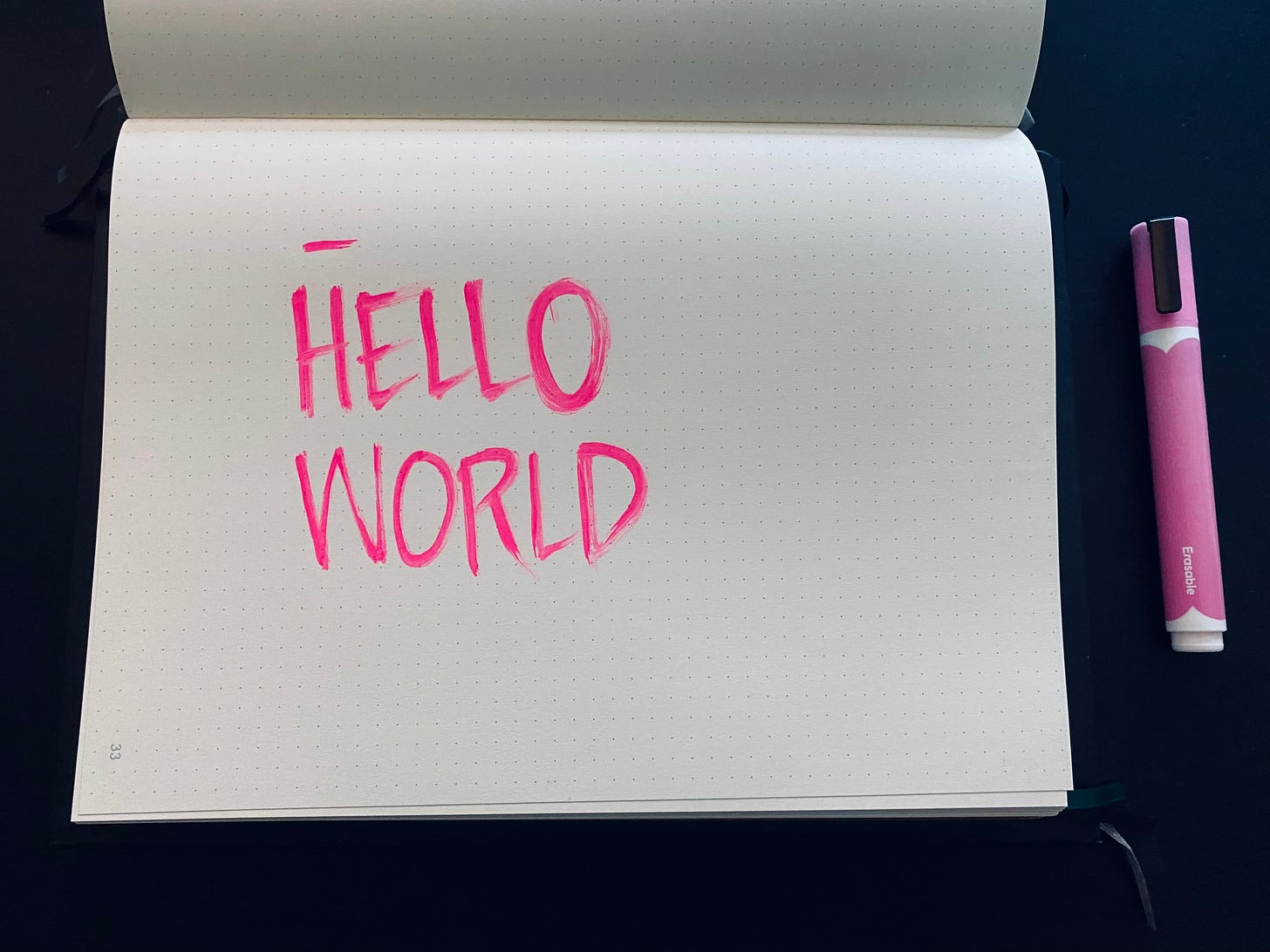 Hello world written in a notebook with a pink paint marker