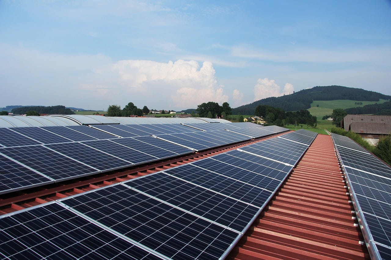 An array of solar panels on a red roof with green hills and a blue sky in the background.