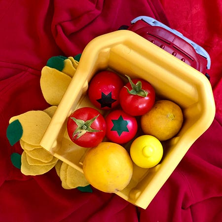 A still photo of a red and yellow plastic dump truck filled with two real tomatoes and two wooden tomatoes, and two real lemons and a wooden lemon, with felt lemons surrounding the truck.