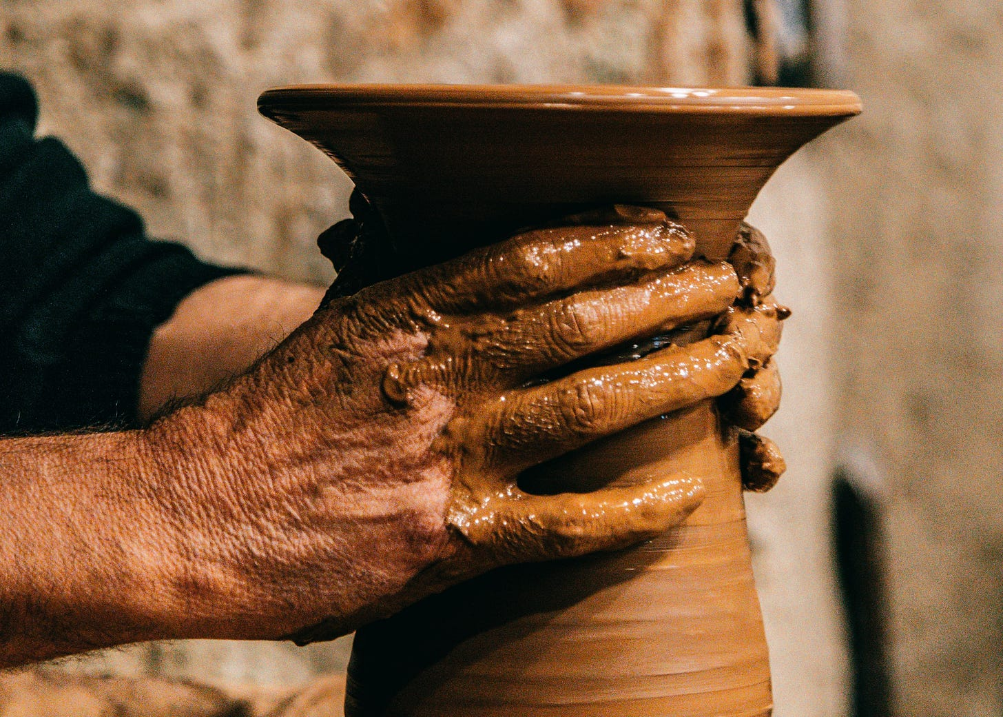Man with hands in clay making vase on pottery wheel