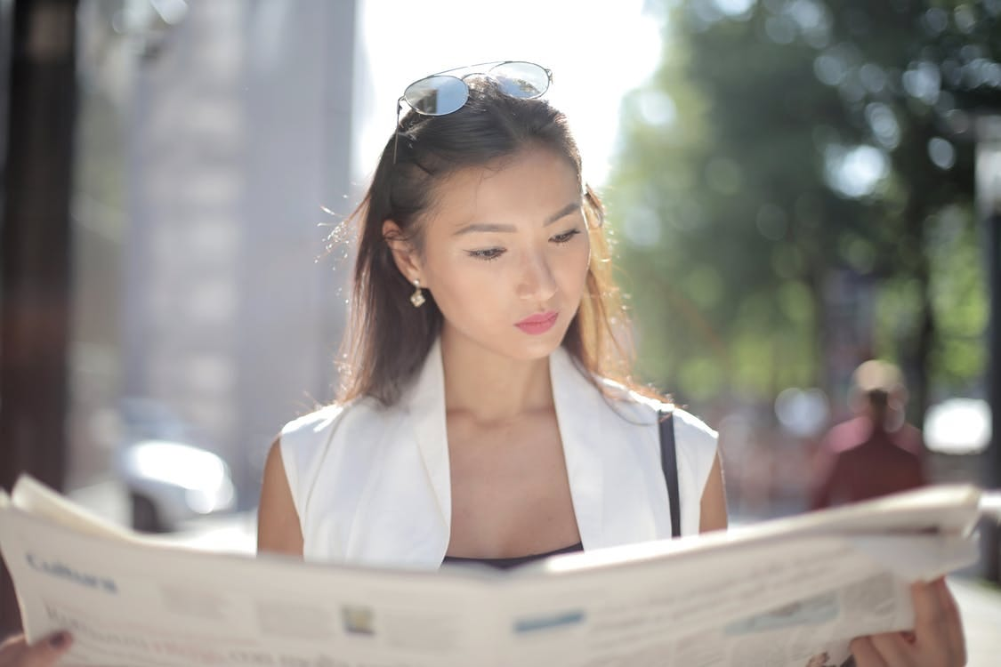 Woman Reading News Outdoors