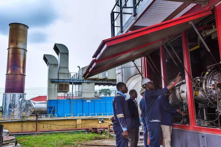 Mechanics attend to a 25-megawatt gas turbine plant that powers the camp
