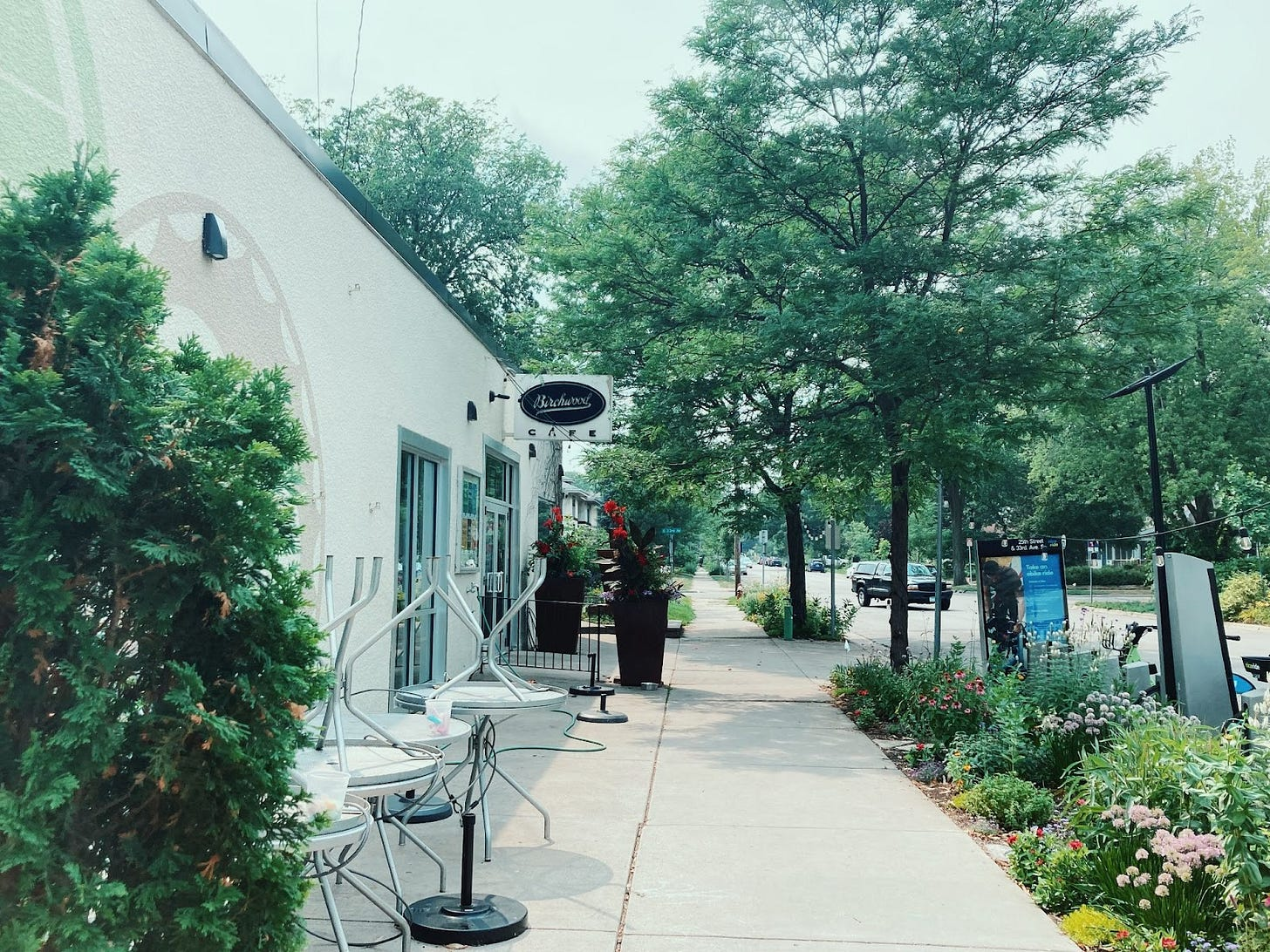 """the front of birchwood cafe, a white building with a white and black sign reading """"Birchwood Cafe"""", surrounded by lush green trees and bushes, and metal chairs and tables stacked to the side"""