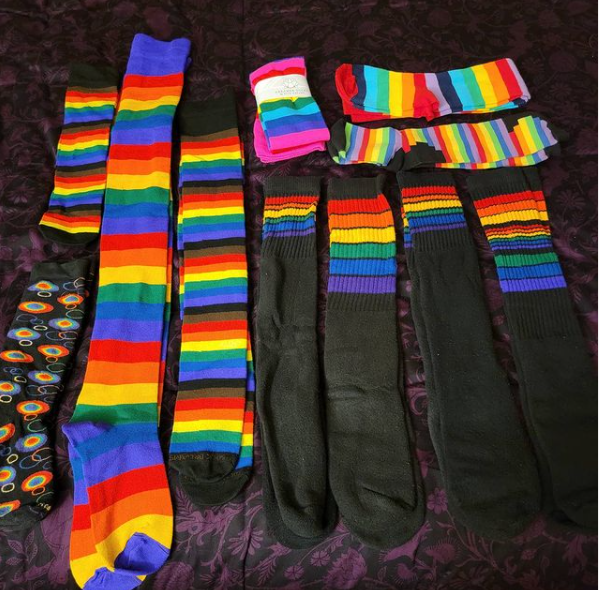 Photo of eleven pairs of various rainbow striped knee socks and thigh-high socks