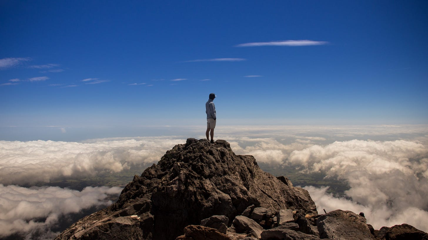 """Man standing on top of a mountain for article titled """"The Psychological Aspects of Optimal Experience"""""""