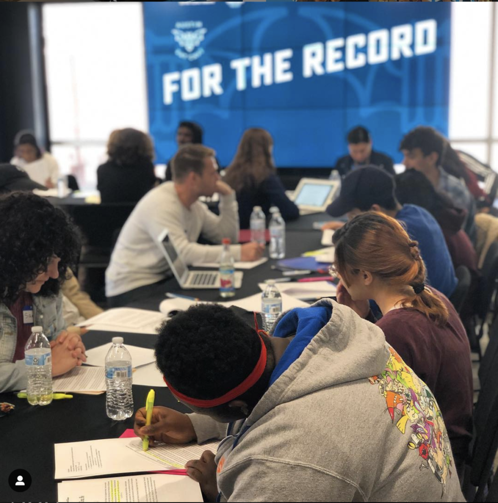 """A photo of a long black table where high school students and instructors are writing on paper and laptops and discussing their work. In the background, there is a large window and a blue banner with """"For the Record"""" across it in bold, white block letters."""