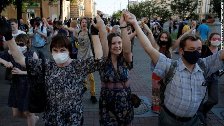 Protesters hold their hands in the air during a rally in Minsk on June 19.