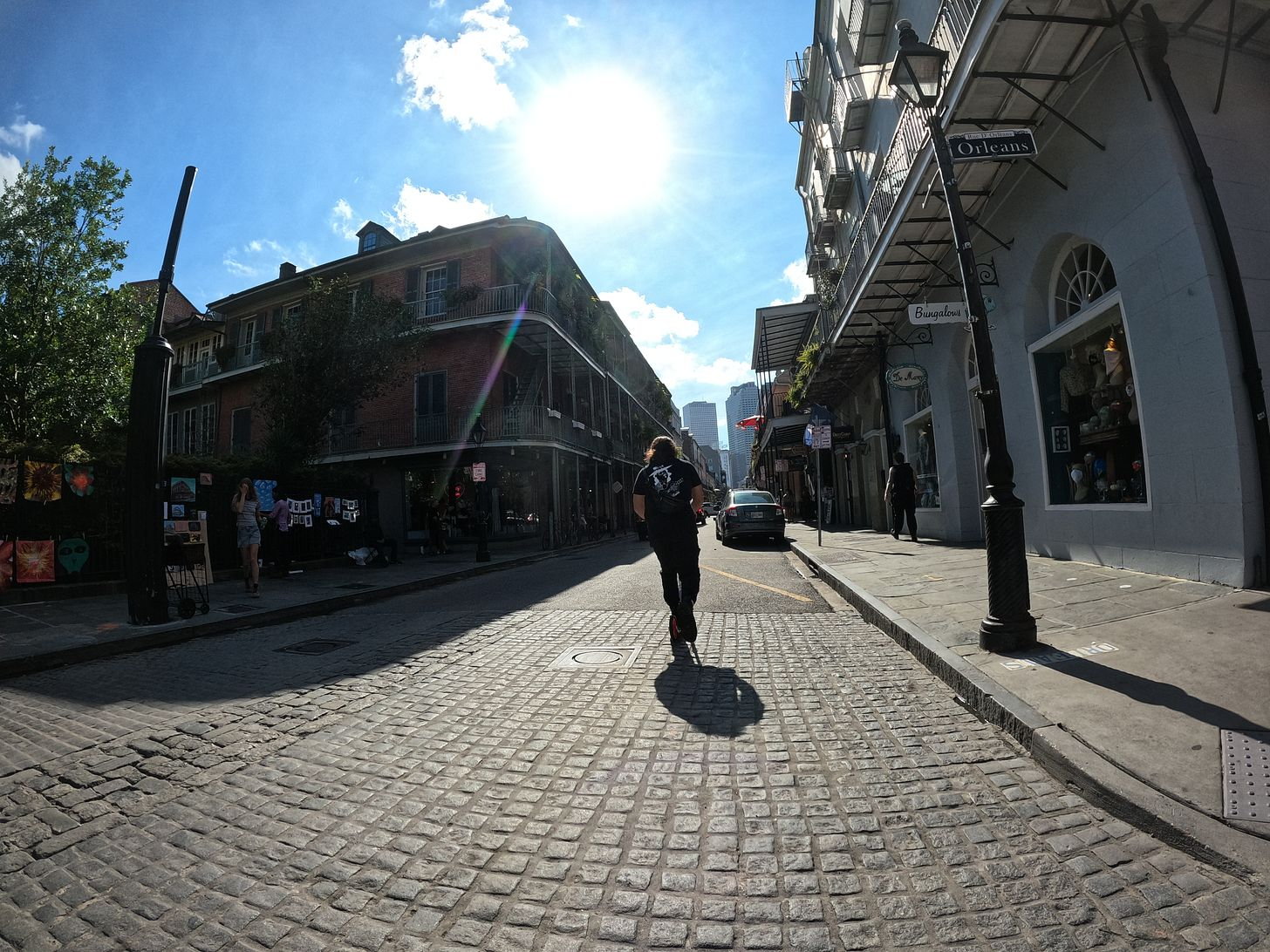 anthony on cobble stone on royal street in new orleans. the sun is bright and you can see a rainbow glare from the sun. Anthony is wearing a stevie ray vaughn shirt and booking it on his scooter in front of kelly