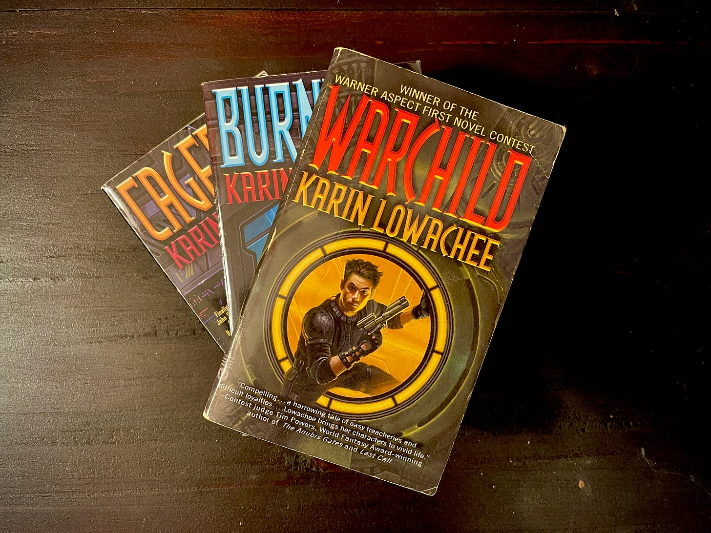 Three books in a spiral stack. The book on the top is Warchild by Karin Lowachee, and features a person on the cover stepping through a portal with a gun.