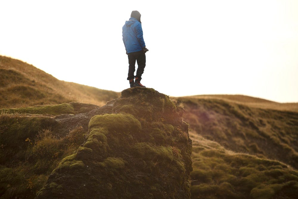 person standing on high ground under white sky