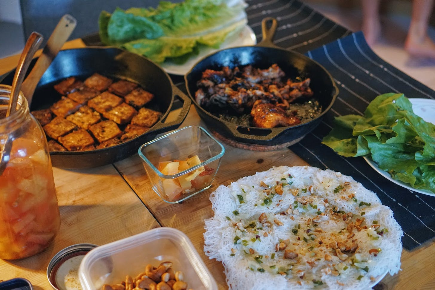 A table filled with plates of vermicelli, tofu, chicken, lettuce and pickles