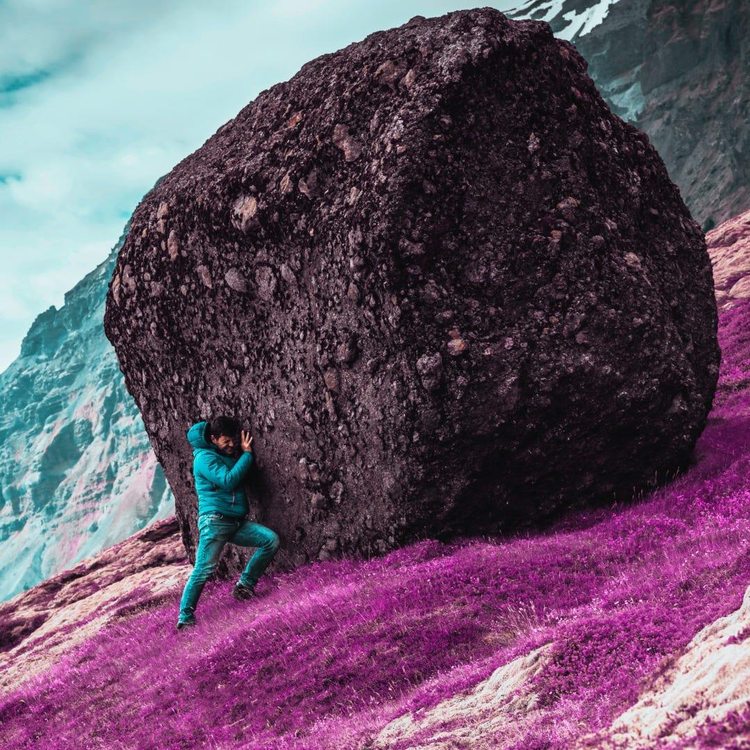 Man pushing large rock uphill