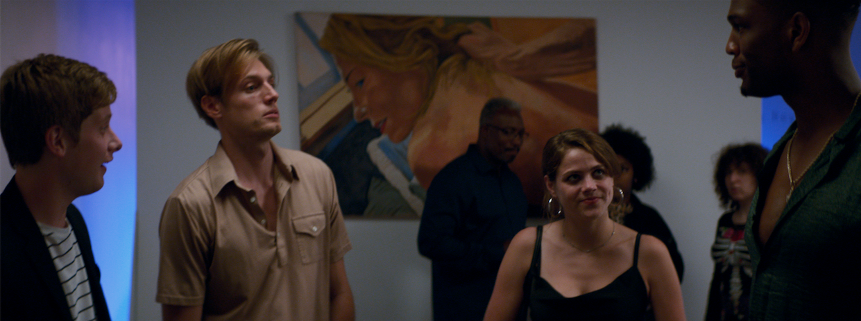 """From the film """"Paint"""": Three men and a yonug woman hold conversation in an art gallery."""