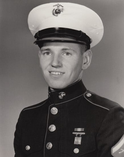 Black and white portrait of a young man wearing a military uniform with a white hat. He has a smile, square chin, young face, and attractive eyes.