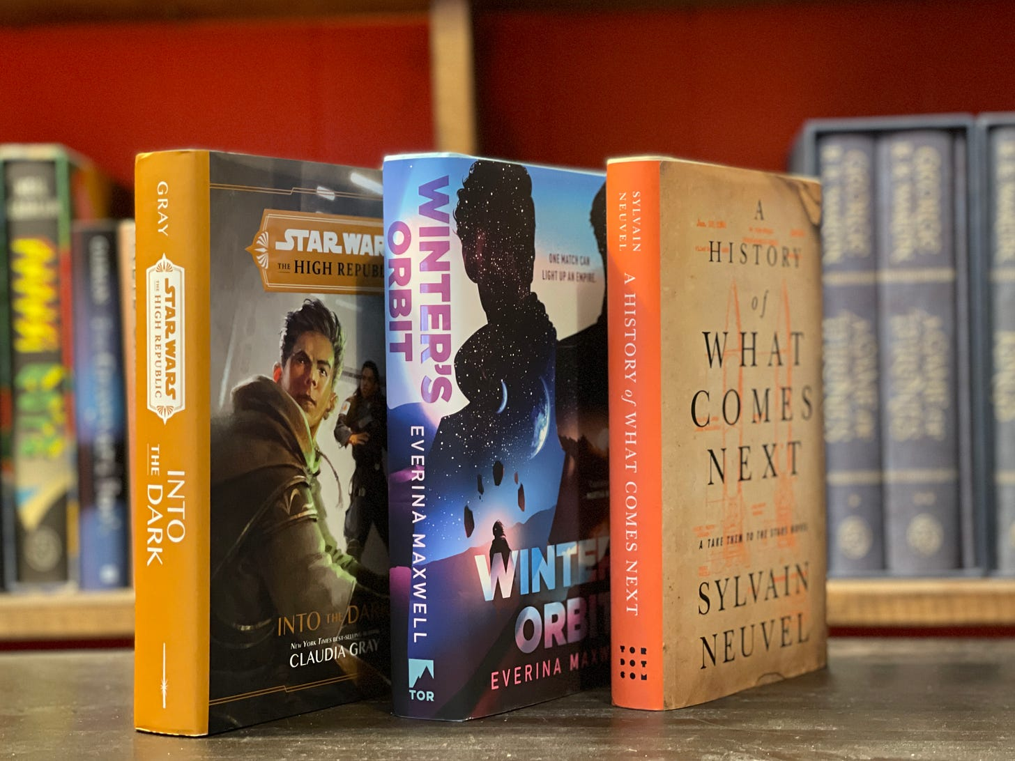 Three books standing on a table: Into the Dark, Winter's Orbit, and History of What Comes Next