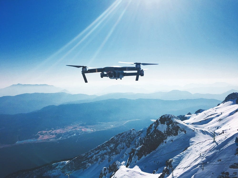 white quadcopter drone flying near snow mountain during daytime