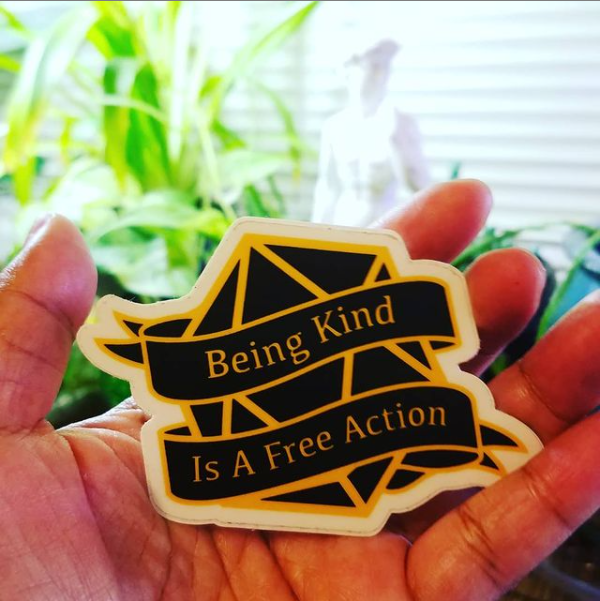 """Photo of my hand holding a sticker. The sticker is in the shape of a black D20 and has the text, """"Being Kind is a Free Action."""" In the background is a replica of the statue of David and some plants."""