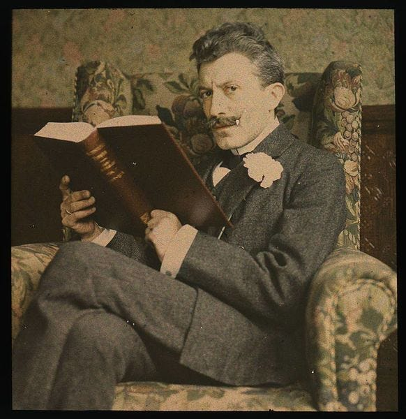 File:Man with book sitting in chair (2677422743).jpg