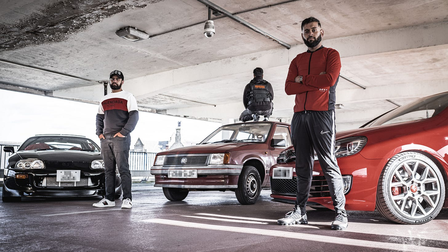 Three Bradford youths of Pakistani origin stand next to their souped-up cars.