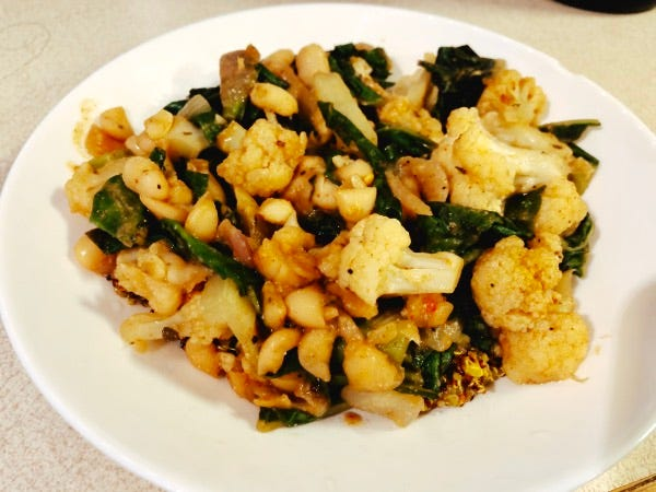 Turmeric Quinoa and Red Beans with Cauliflower and Chard from the How Not to Diet cookbook in a white bowl.