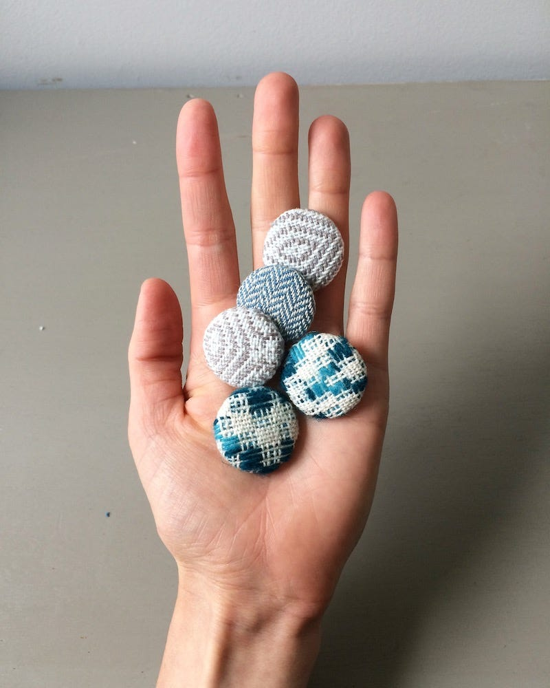 A hand holding five multi-coloured fabric covered buttons in a flat palm