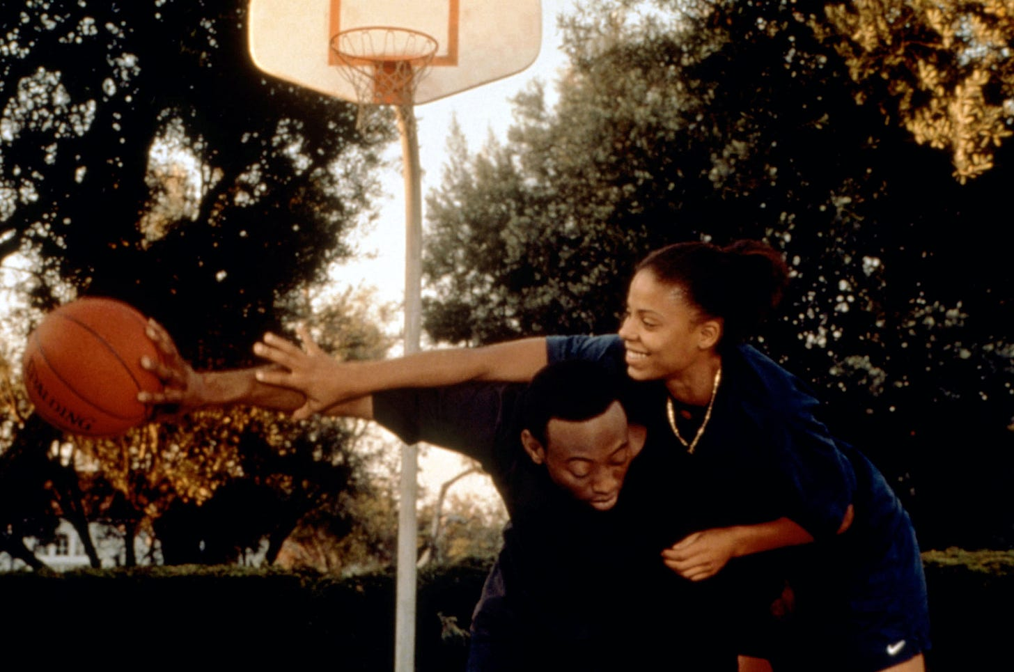 The two characters of love and basketball playing basketball. She is reaching over his back trying to grab the ball which he is holding at arm's length.