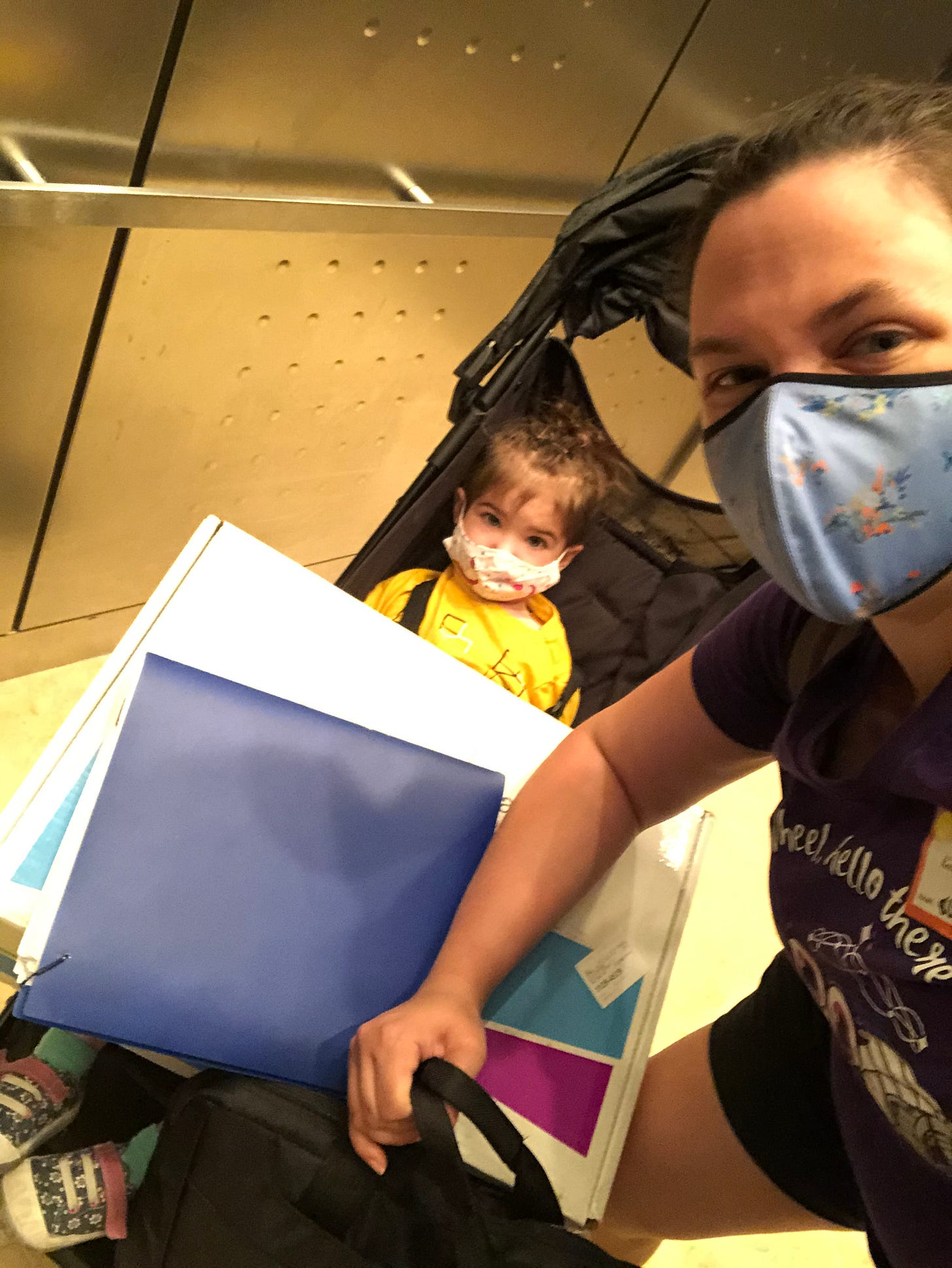 Photo of mom and child in an elevator, the child has an enormous box on her lap.